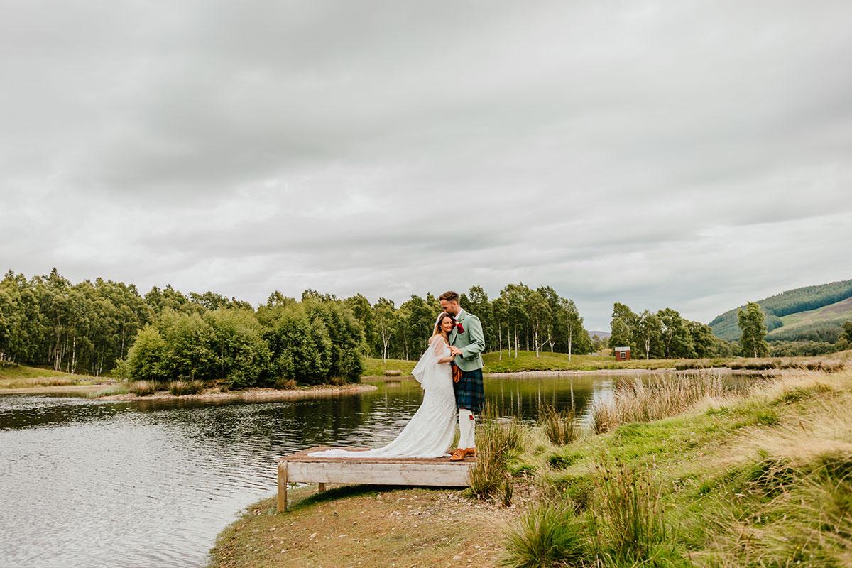 bride and groom standing on loch jetty at Glen Clova