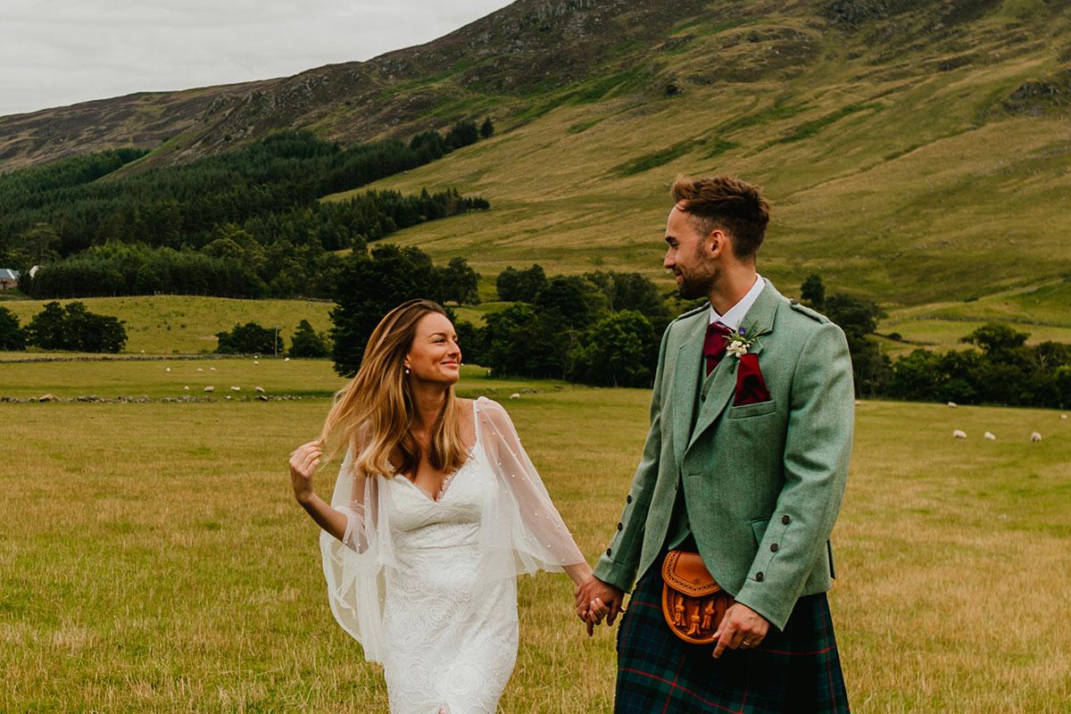 bride and groom holding hands walking in field at Glen Clova