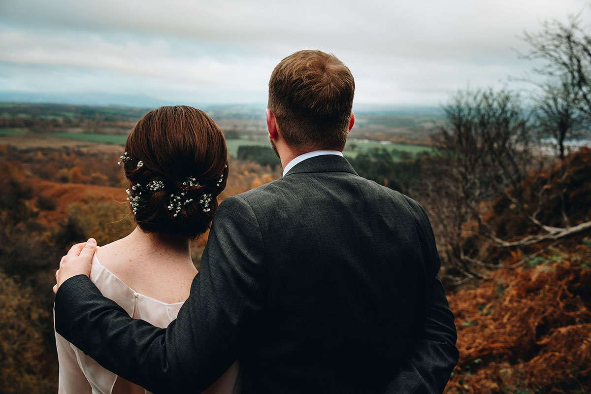 bride and groom look out from the top of Conic Hill