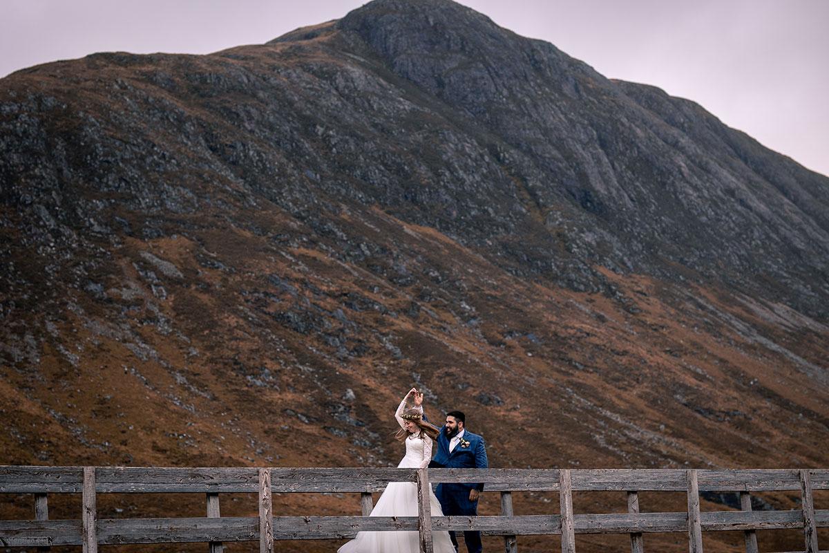 bride and groom dancing on bridge in Glencoe