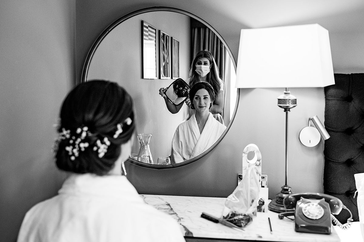 bride being shown hair in mirror by hairdresser on morning of wedding