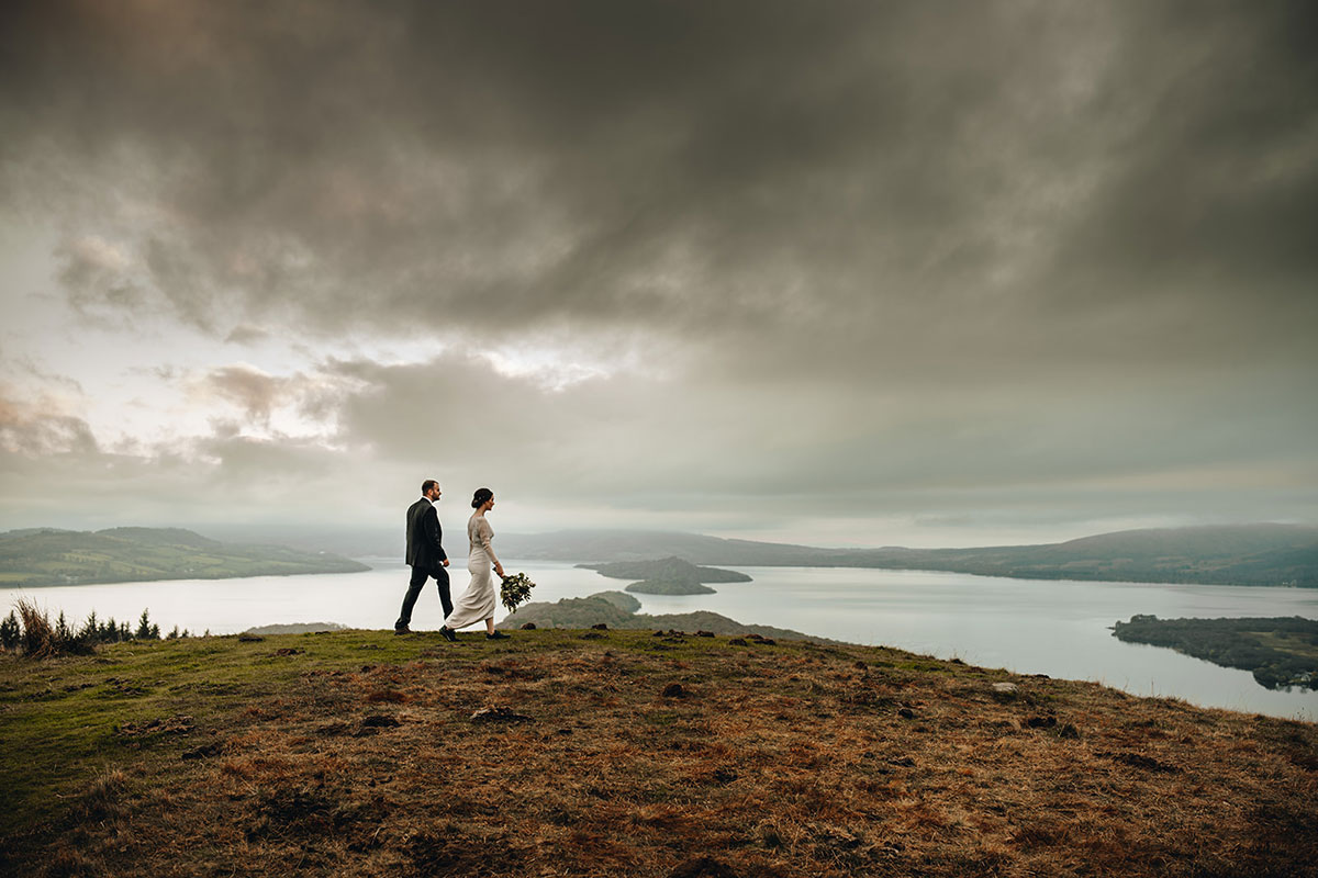 bride and groom walk across the top of Conic Hill with Loch Lomond in the background