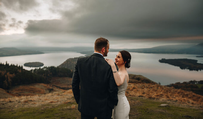 bride and groom look into each other's eyes and smile on the top of Conic Hill Loch Lomond