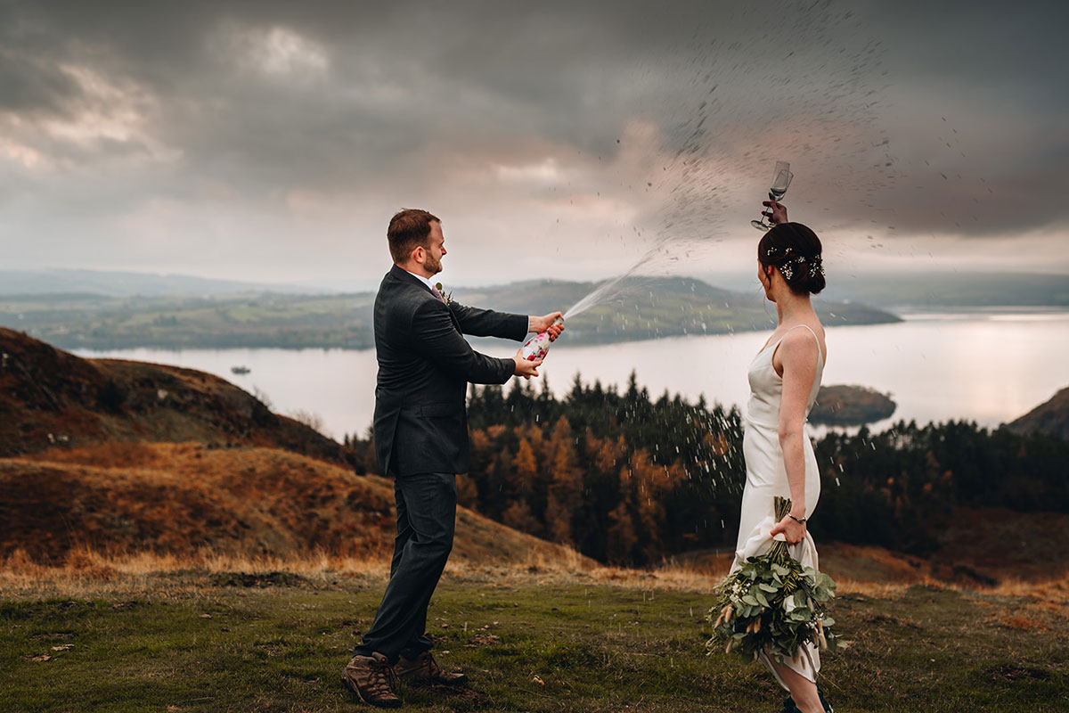 bride and groom pop the cork on a bottle of fizz on the top of Conic Hill Loch Lomond