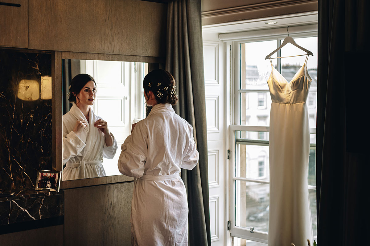 bride wearing bathrobe looking in mirror fixing necklace at Kimpton Blythswood Square hotel