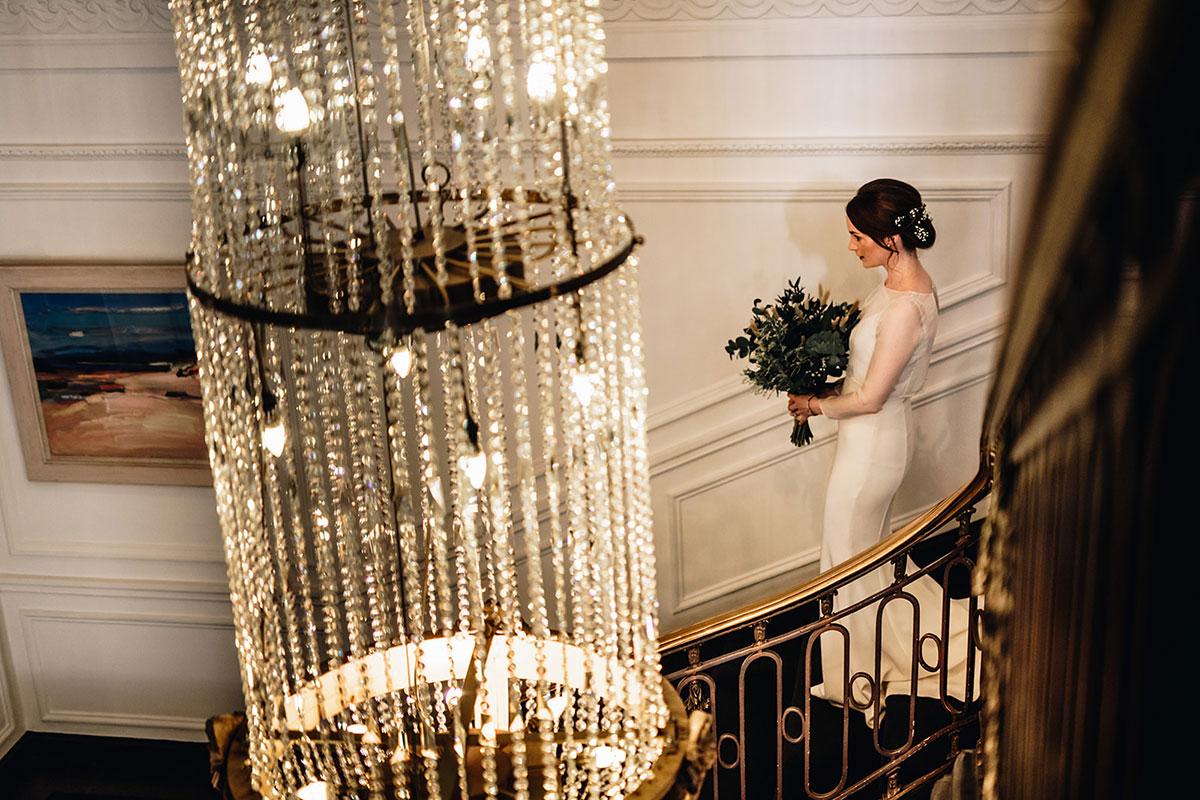 bride walking down stairs at Kimpton Blythswood Square Glasgow hotel
