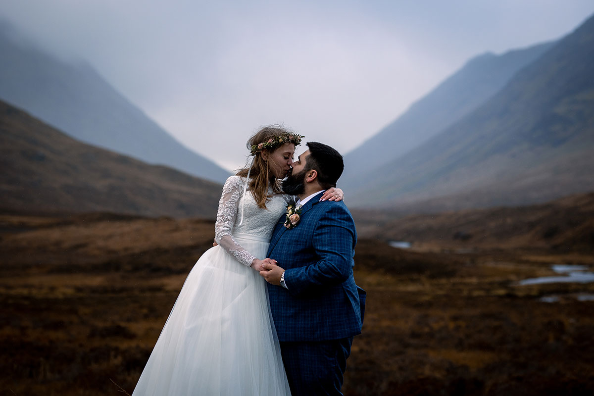 bride and groom kissing in mountains of Glencoe Scotland