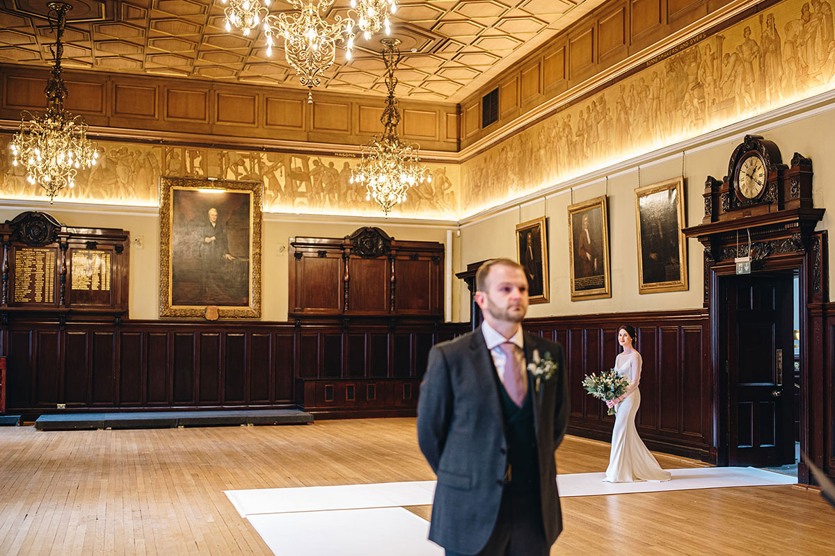 bride entering room at Trades Hall Glasgow with groom waiting at top of aisle