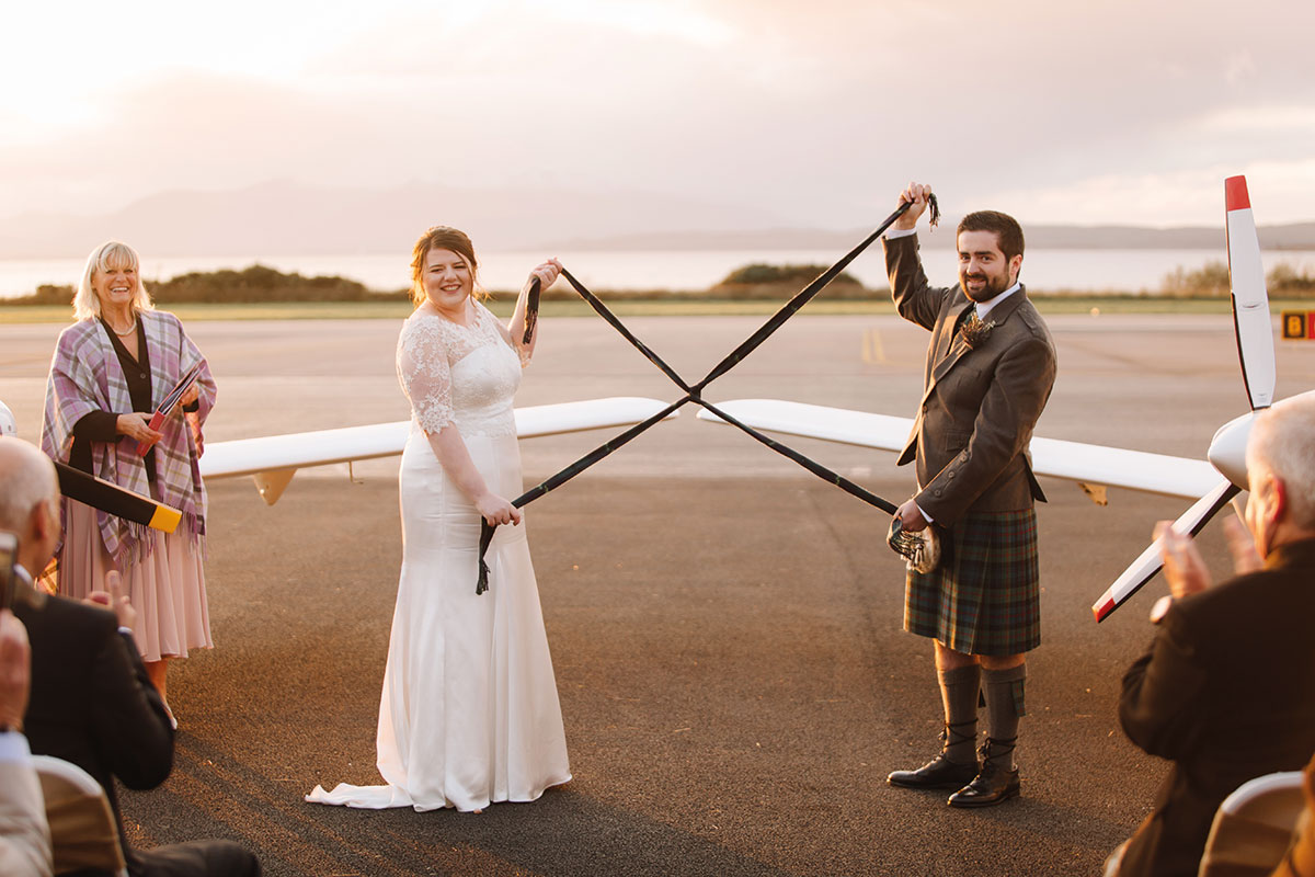 Bride and groom performing a hand-fasting with tartan ribbons on the tarmac at Oban Airport