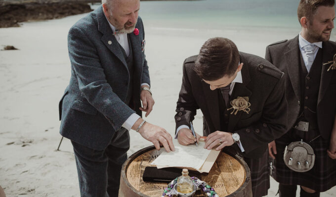 Groom signing wedding schedule with guidance from celebrant on the beach at Eriskay