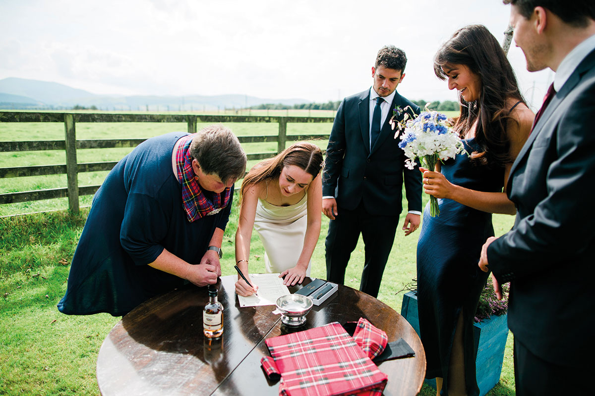 Bride signing wedding schedule outside at Cormiston Farm with celebrant, groom and two witnesses looking on