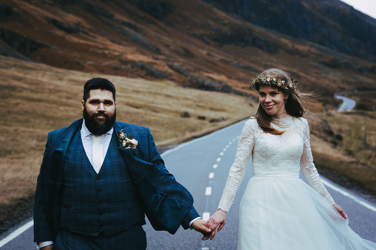 bride and groom walking on A82 in Glencoe Scotland by Lewis Cannon Photography