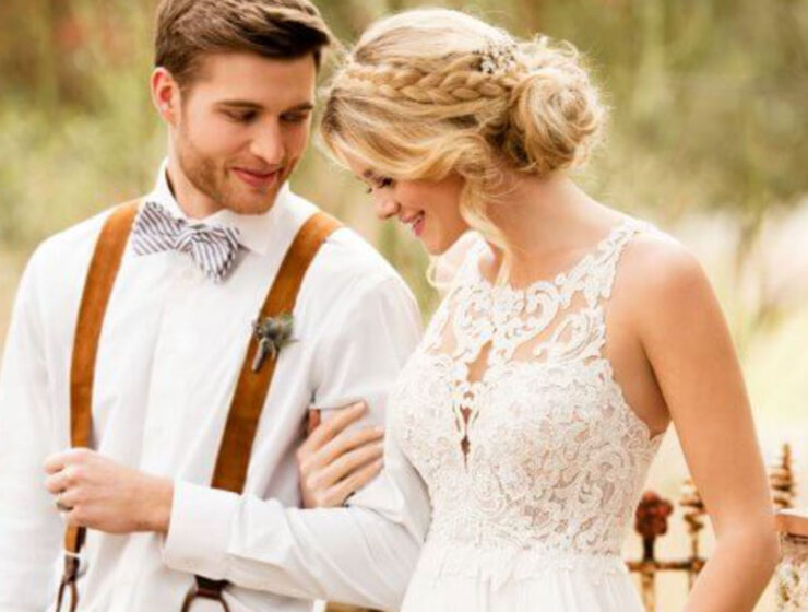 Model wearing Essense of Australia wedding dress from Kudos Bridal Boutique in Edinburgh walking with groom wearing bow tie and braces