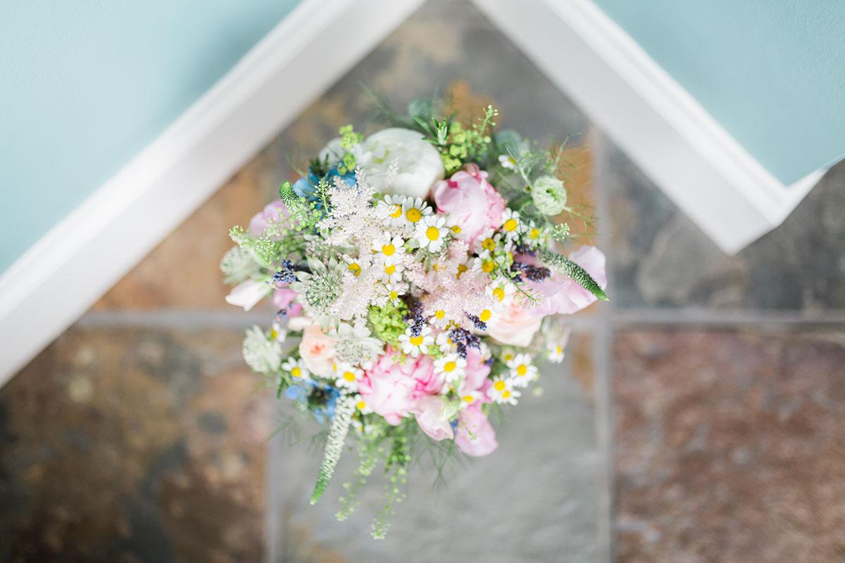 daisy and ranunculus wedding bouquet on tiled floor