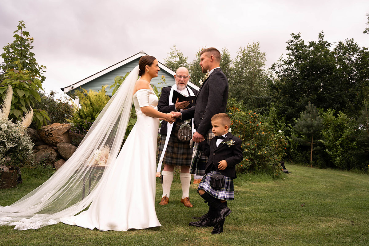 bride, groom and son holding hands in front of minister during outdoors wedding ceremony in Perthshire