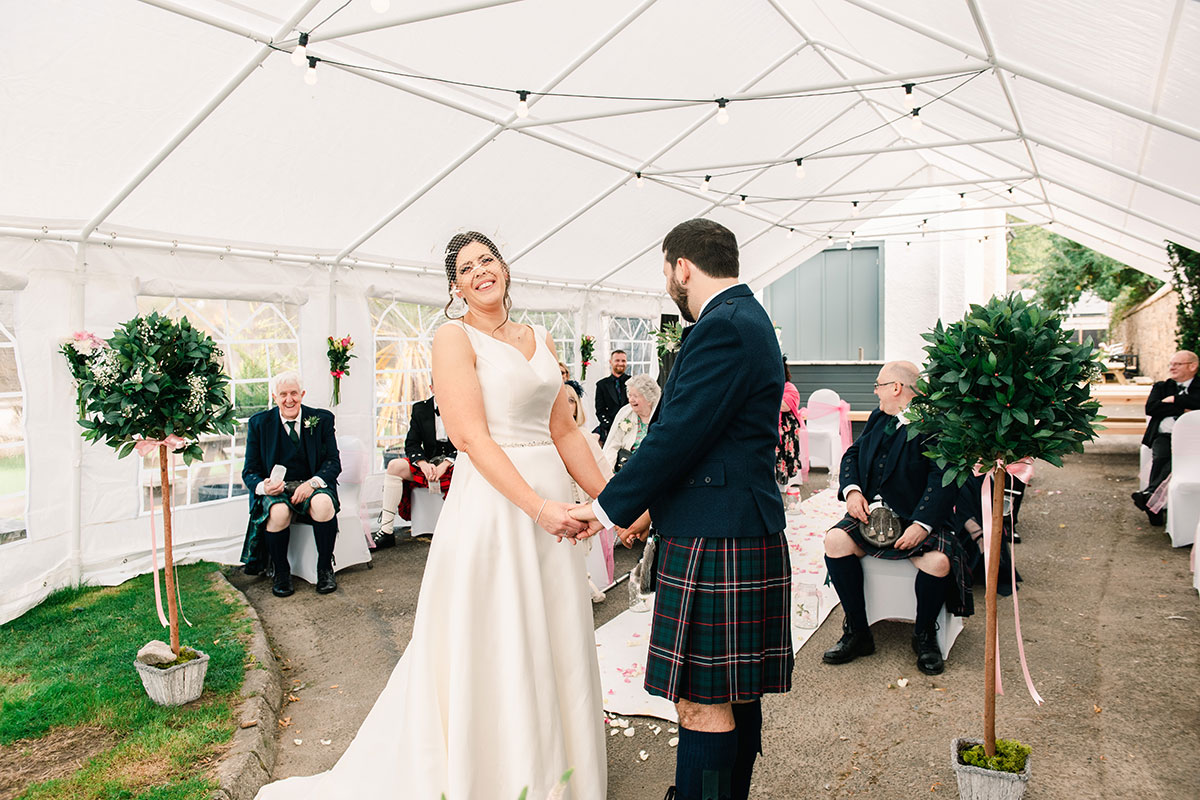 bride laughing during marquee wedding ceremony at Waterside Hotel Inverness