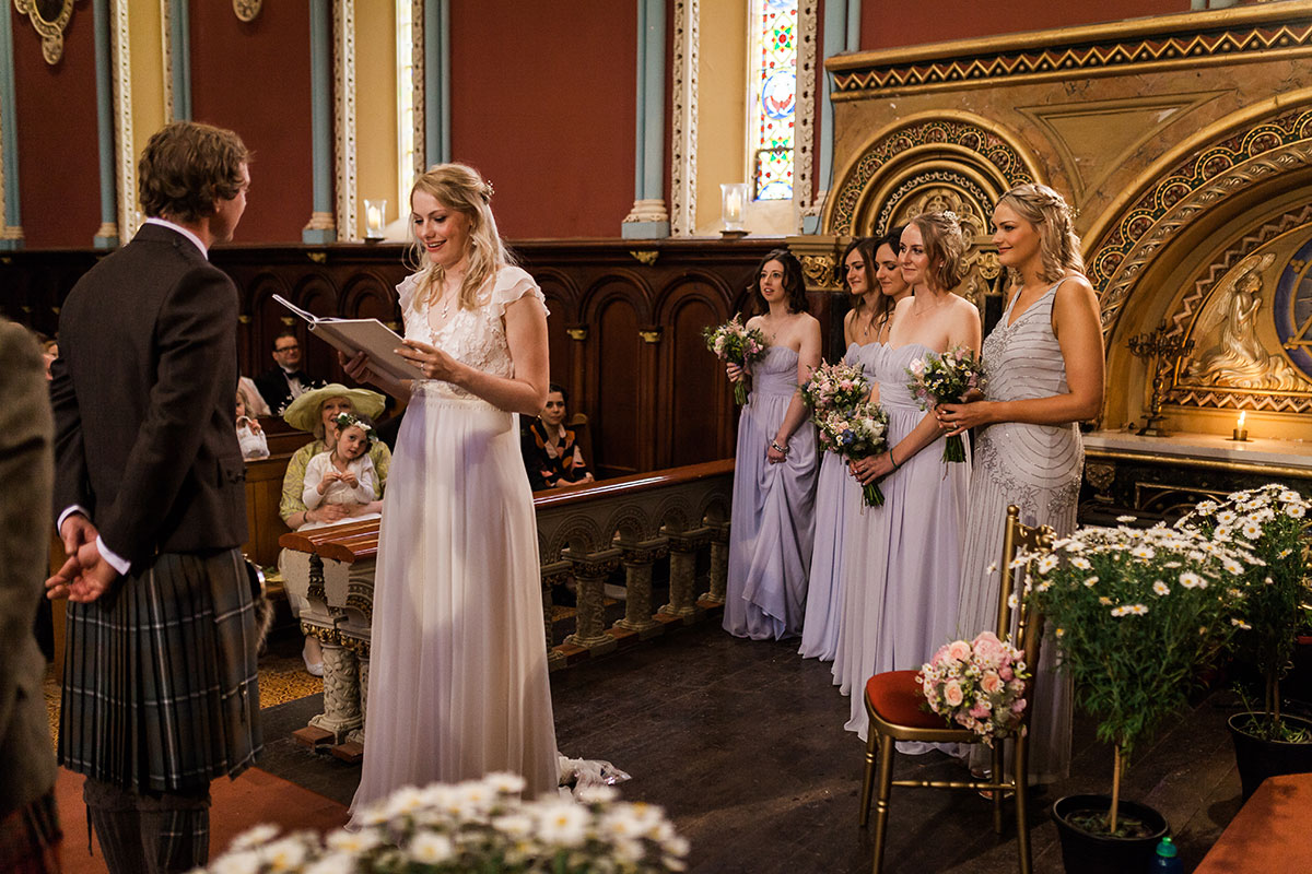 bride reading vows to groom with bridesmaids looking on