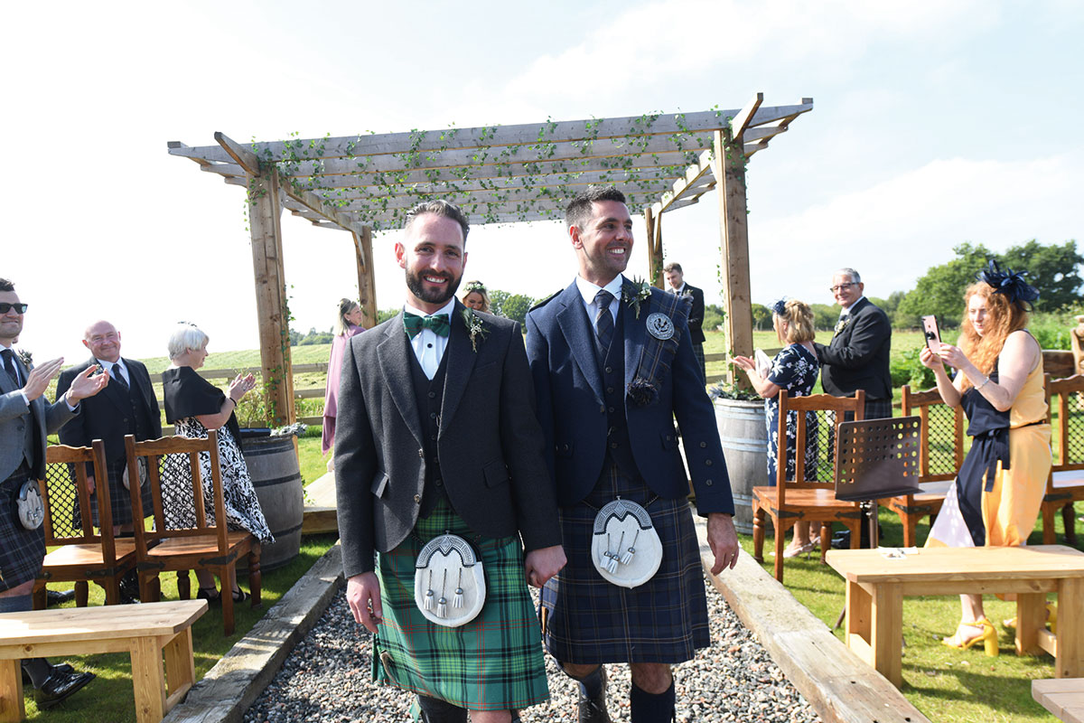 two newlywed grooms wearing kilts at same sex outdoor wedding at the Gathering