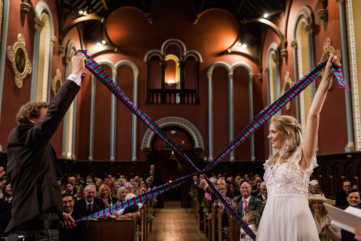 bride and groom performing hand fasting with tartan ribbons at Murthly Castle wedding ceremony