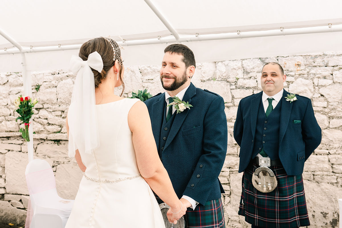 groom smiling holding bride's hands during marquee wedding ceremony at Waterside Hotel Inverness