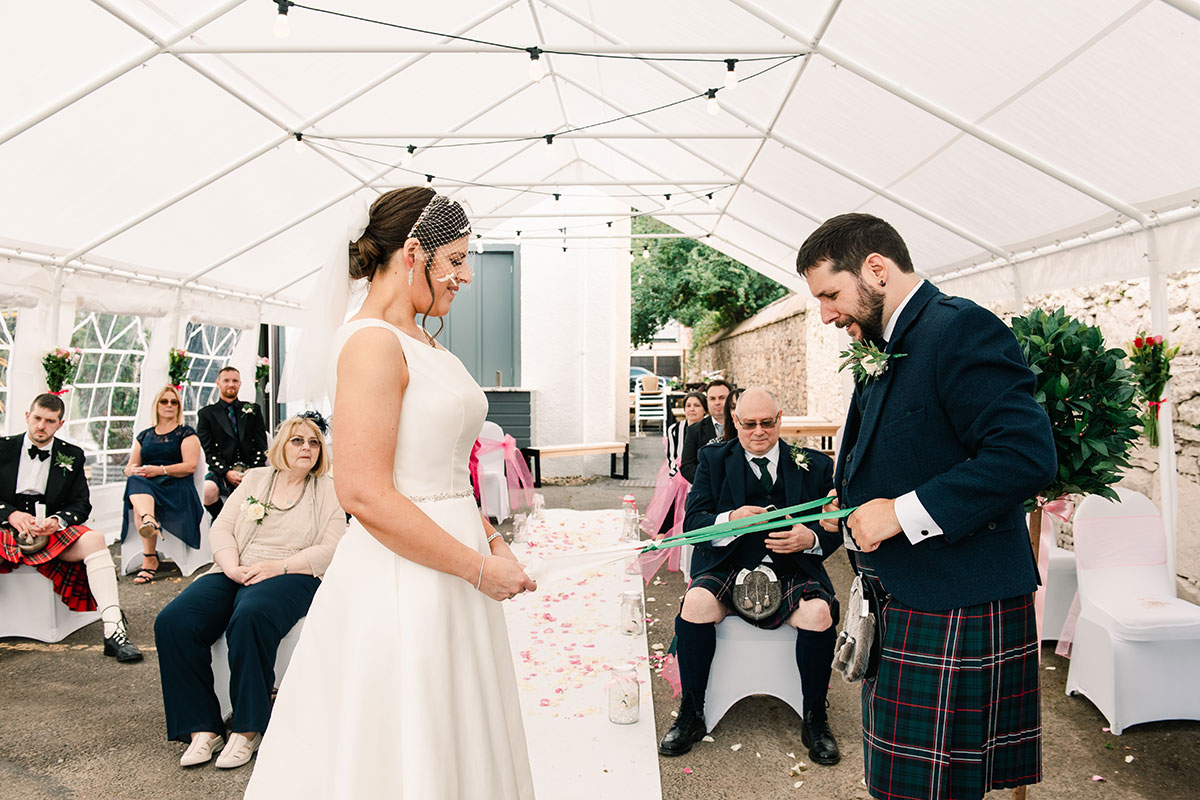 bride and groom performing handfasting with tartan ribbon during marquee wedding ceremony at Waterside Hotel Inverness