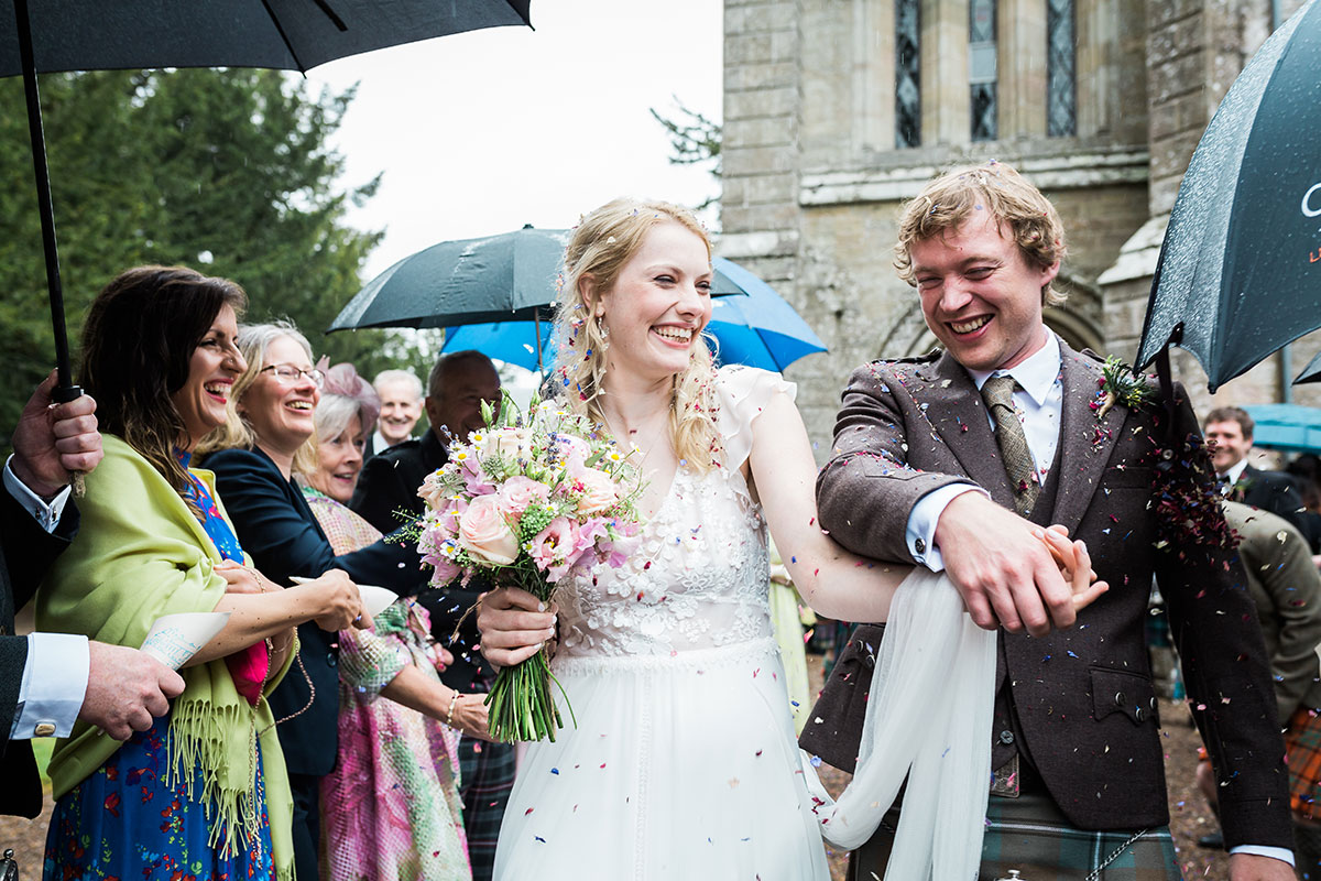 bride and groom showered in confetti outside Murthly Castle wedding chapel