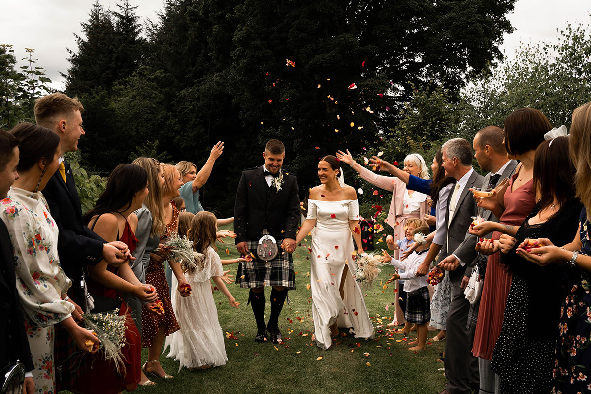 bride and groom walking hand in hand with guests throwing confetti