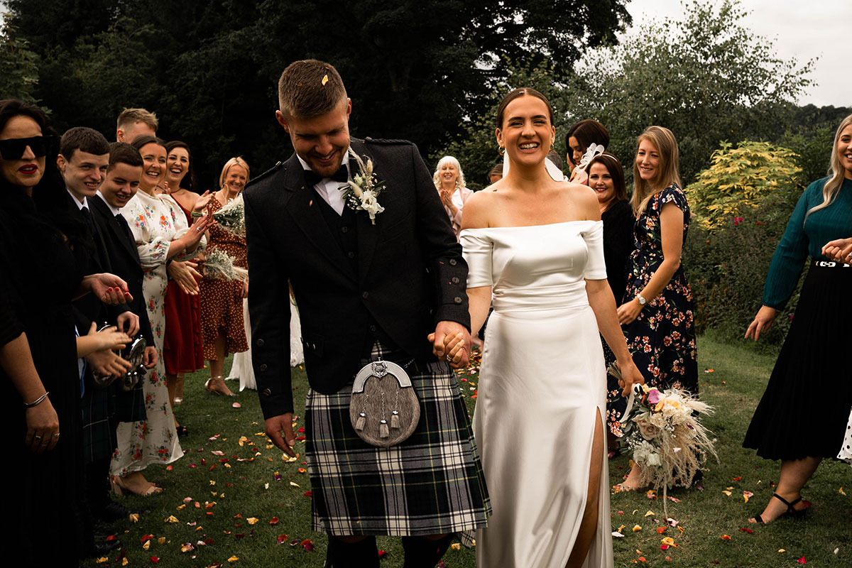 bride and groom smiling hand in hand after guests throwing confetti