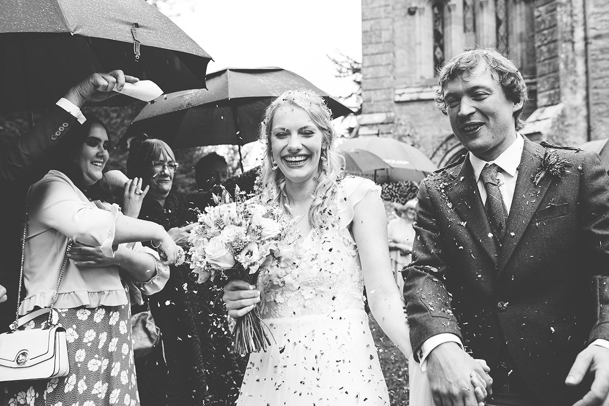 bride and groom showered in confetti and smiling outside Murthly Castle wedding chapel.