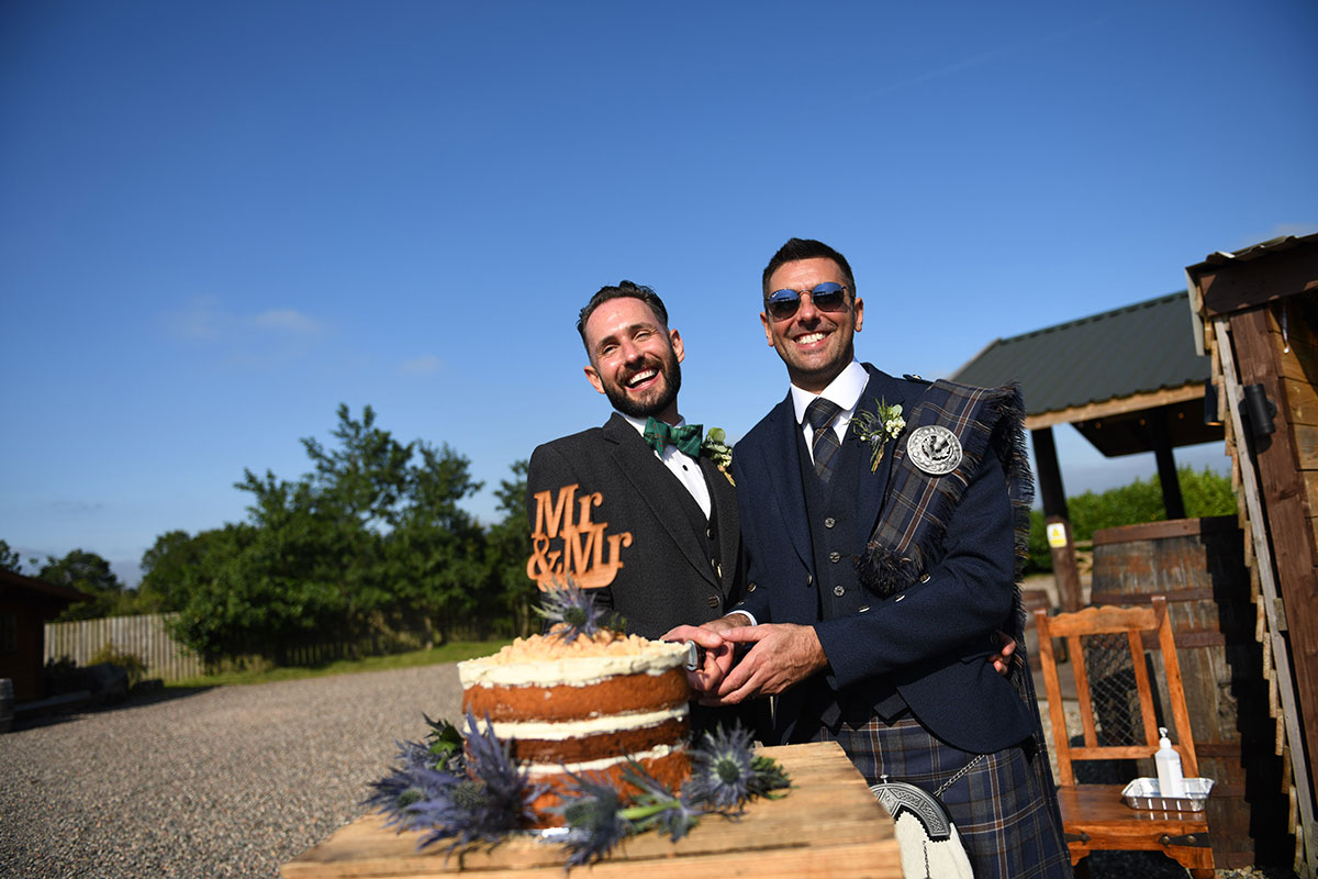 two grooms cutting wedding cake with blue skies outdoors at The Gathering