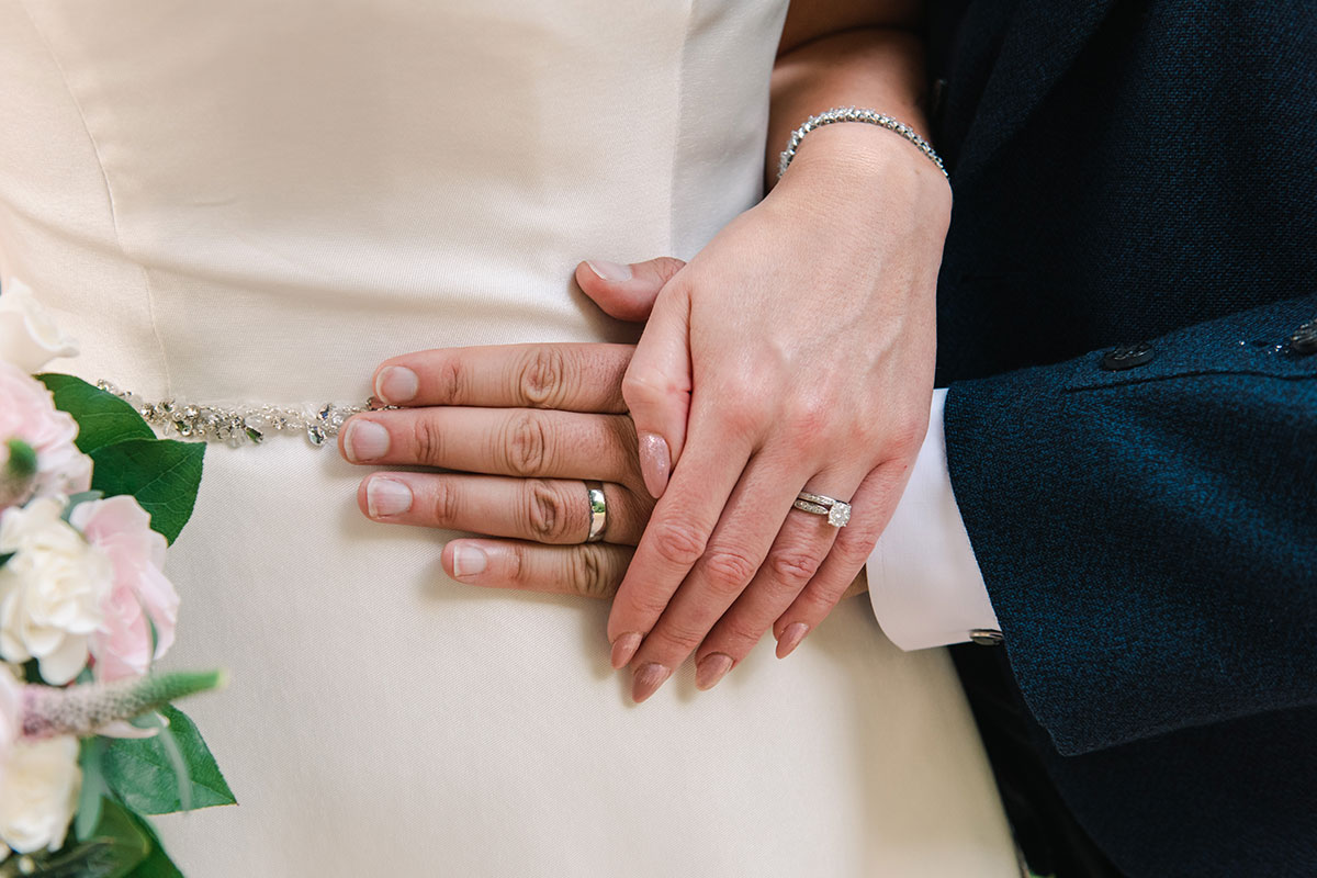 bride and groom hands wearing rings from Chisholm Hunter