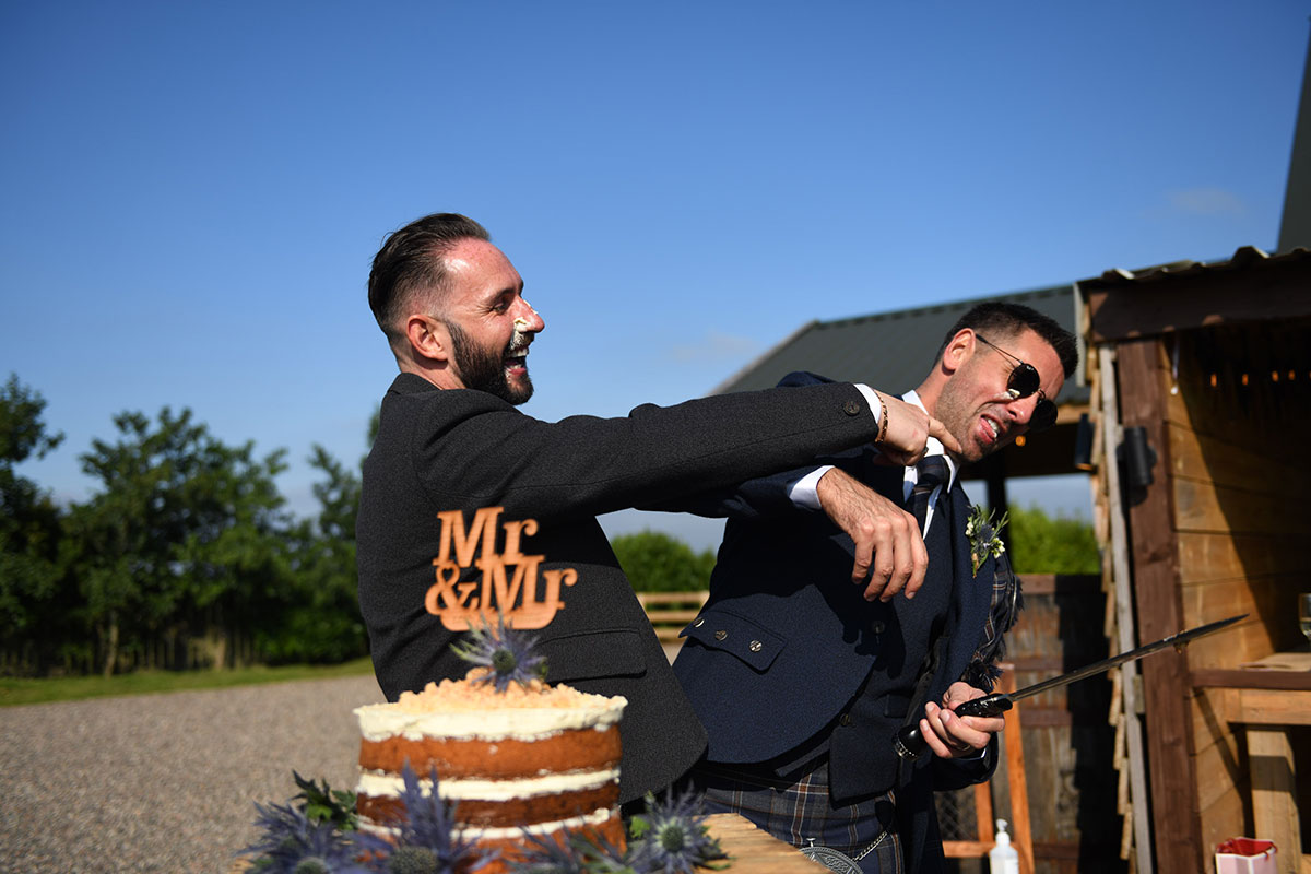 one groom forcing icing from wedding cake on new husband's face outdoors at The Gathering