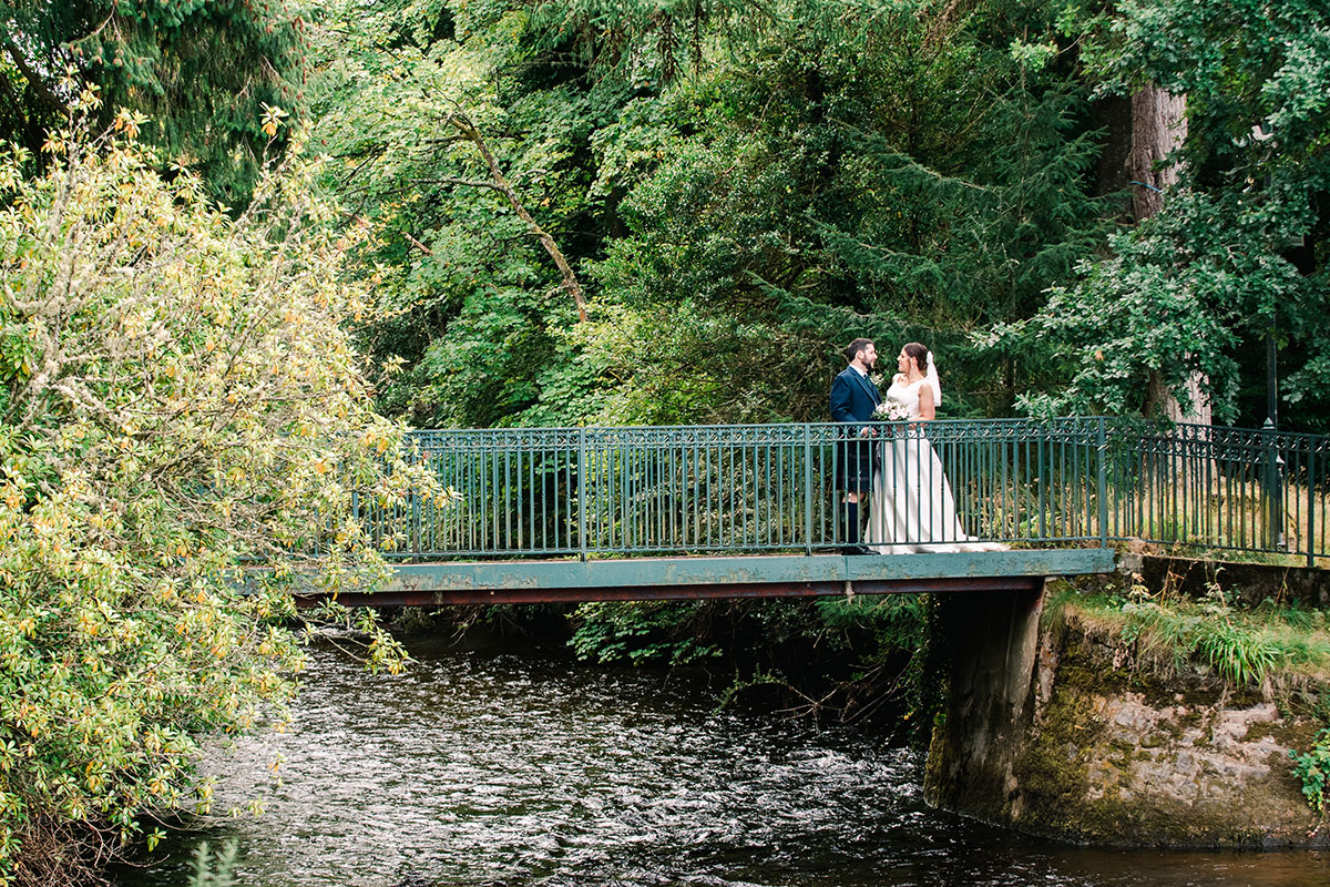 bride and groom standing on green footbridge over the River Ness Inverness