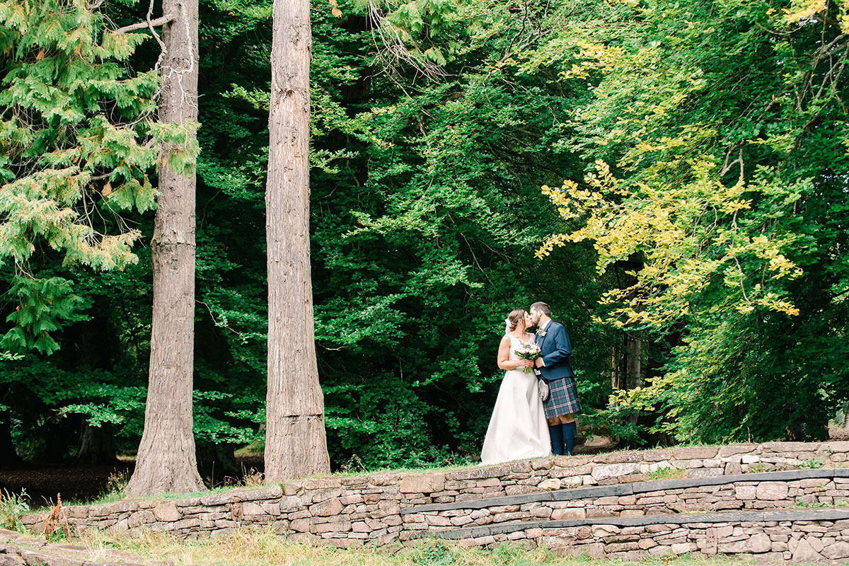 bride and groom kissing surrounded by trees in Inverness