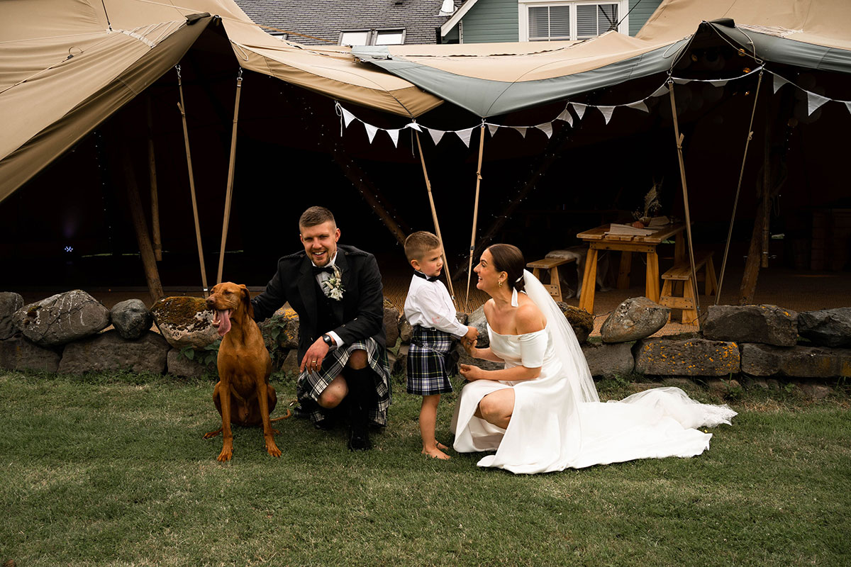 crouching groom with dog and crouching bride talking to young son wearing kilt