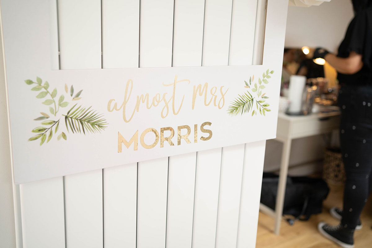 Almost Mrs Morris fern leaf and gold letter wedding sign hanging on white door