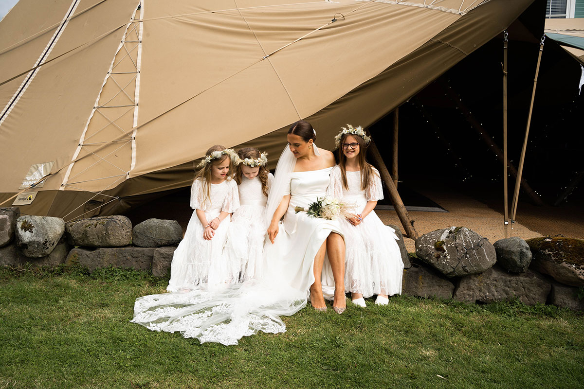 bride and three flower girls sitting on wall outside teepee