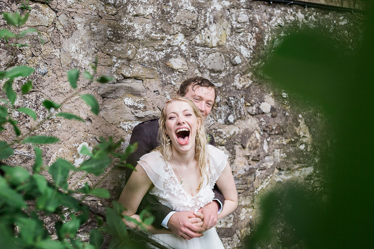 groom hugging bride around waist and bride laughing against wall at Murthly Castle