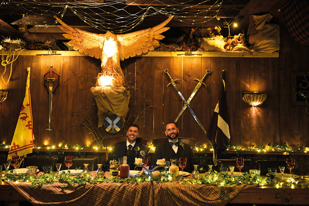 two grooms seated for dinner at illuminated top table at The Gathering with swords and flags