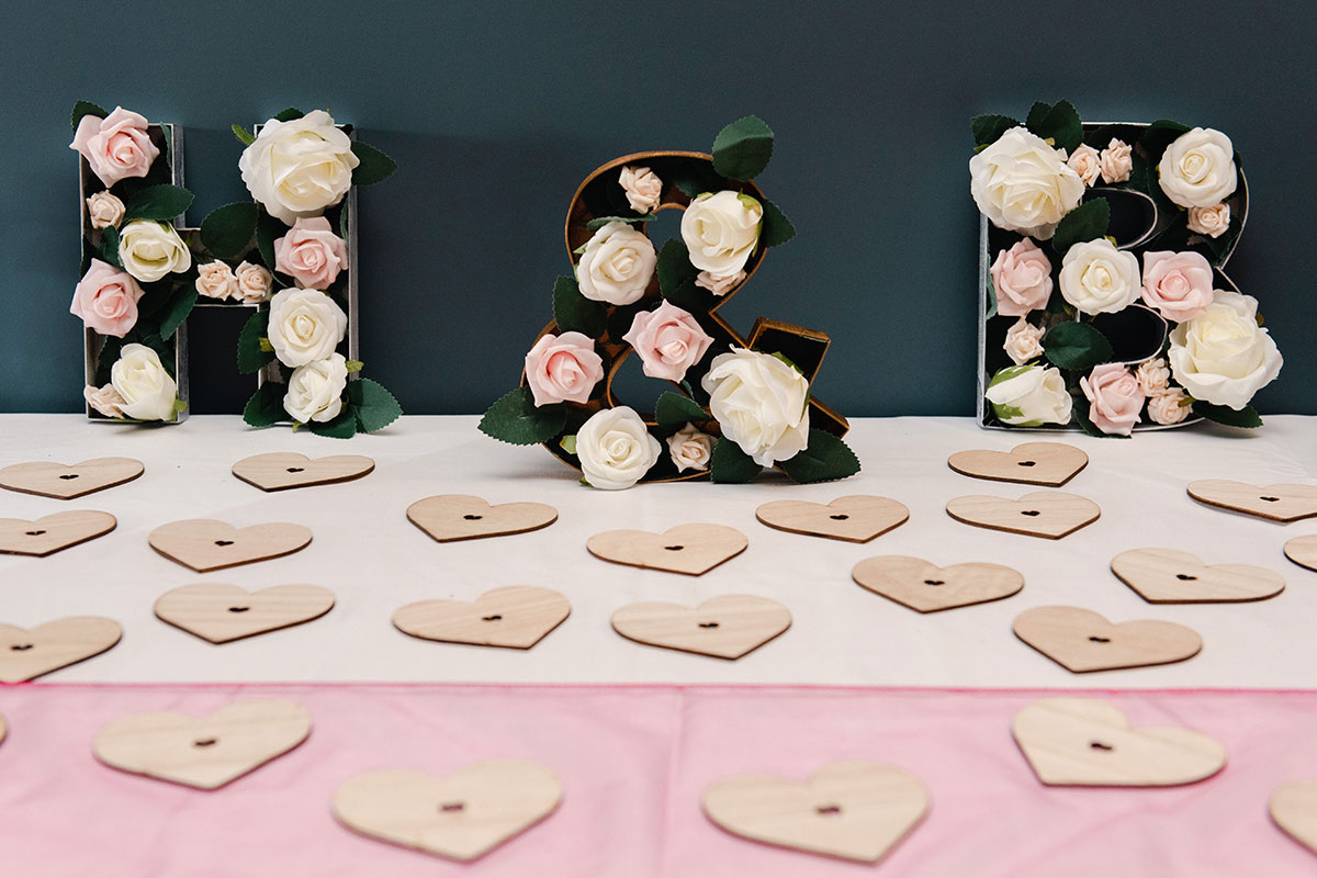 flower-filled letters with wooden hearts wedding table decoration