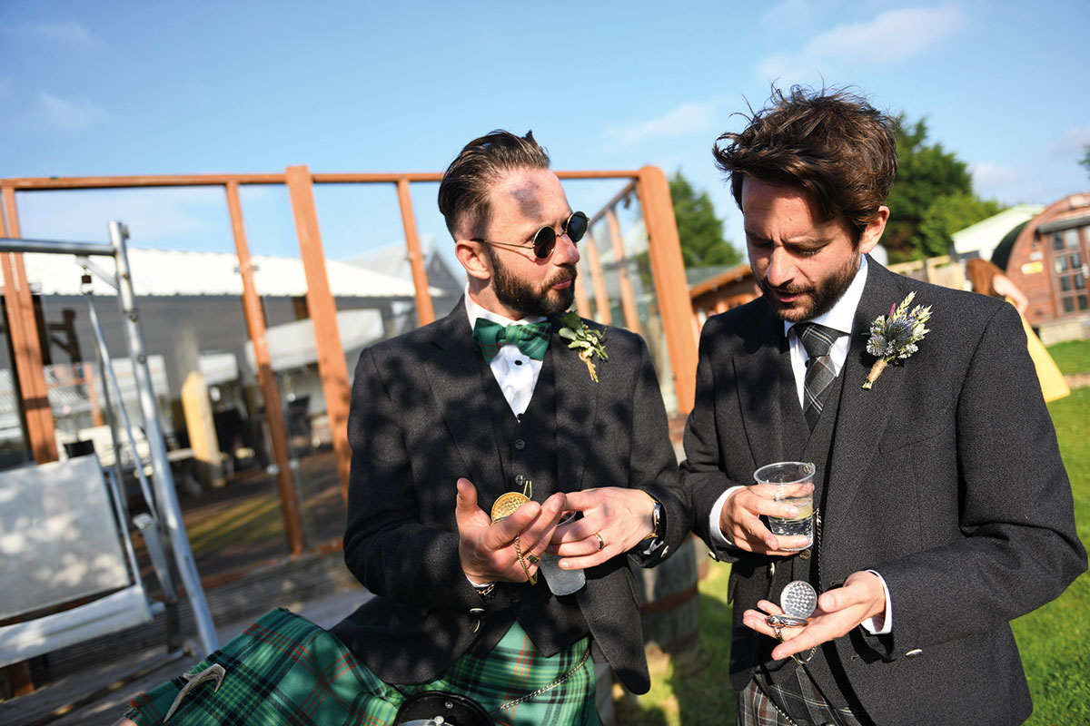 groom showing pocket watch to other male guest at outdoors same-sex wedding at the Gathering