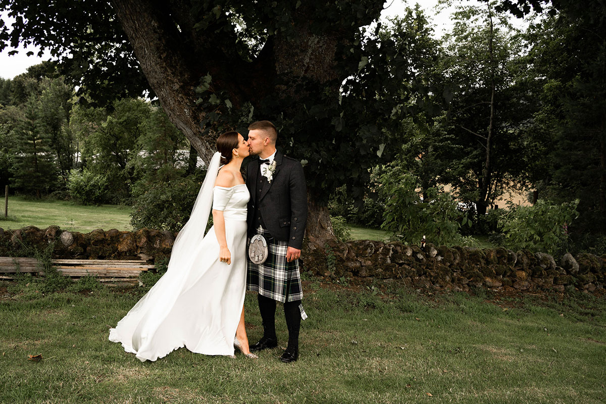 bride and groom kissing each other standing by a tree