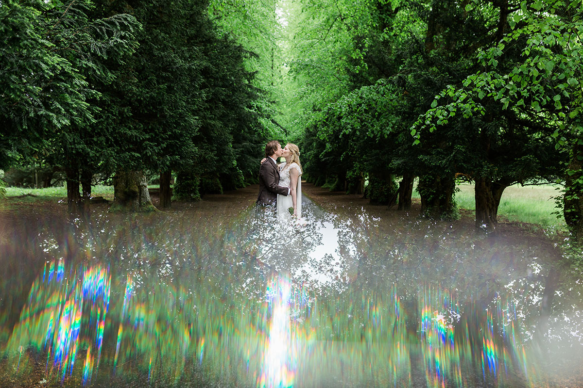 bride and groom on tree-lined driveway with reflection effect from puddle