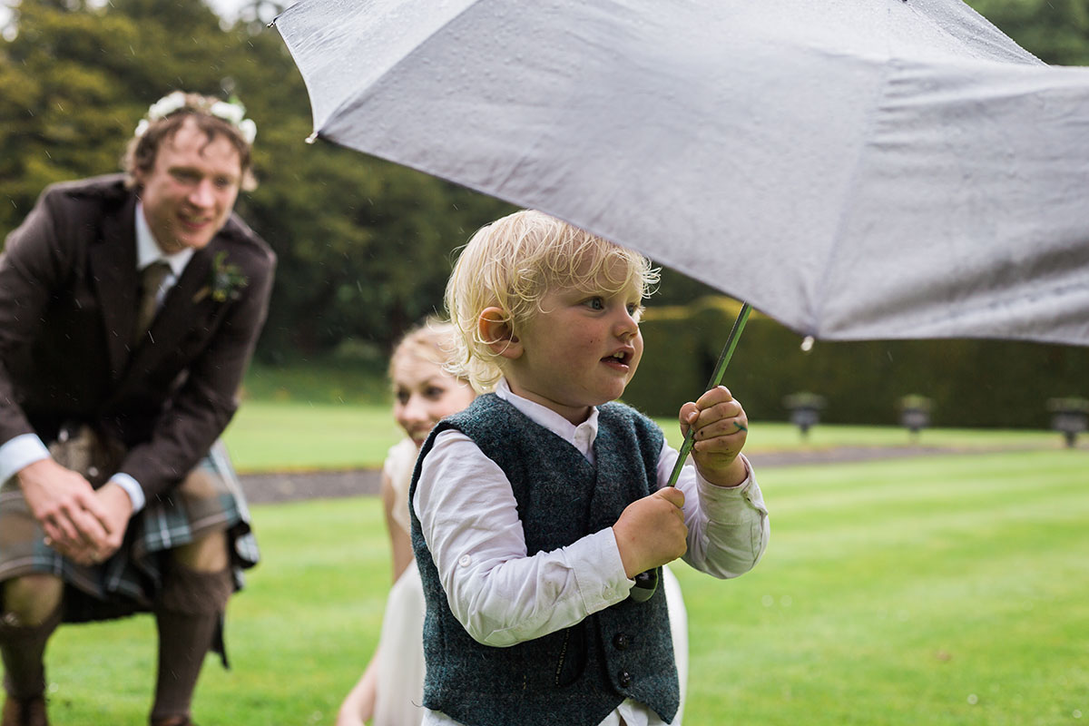 bride and groom watching toddler son hold umbrella at wedding