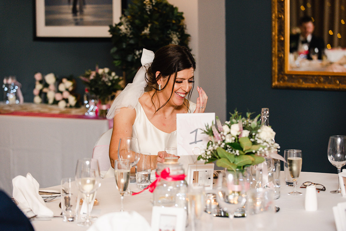 bride laughing during wedding speech at dinner table at Waterside Hotel Inverness