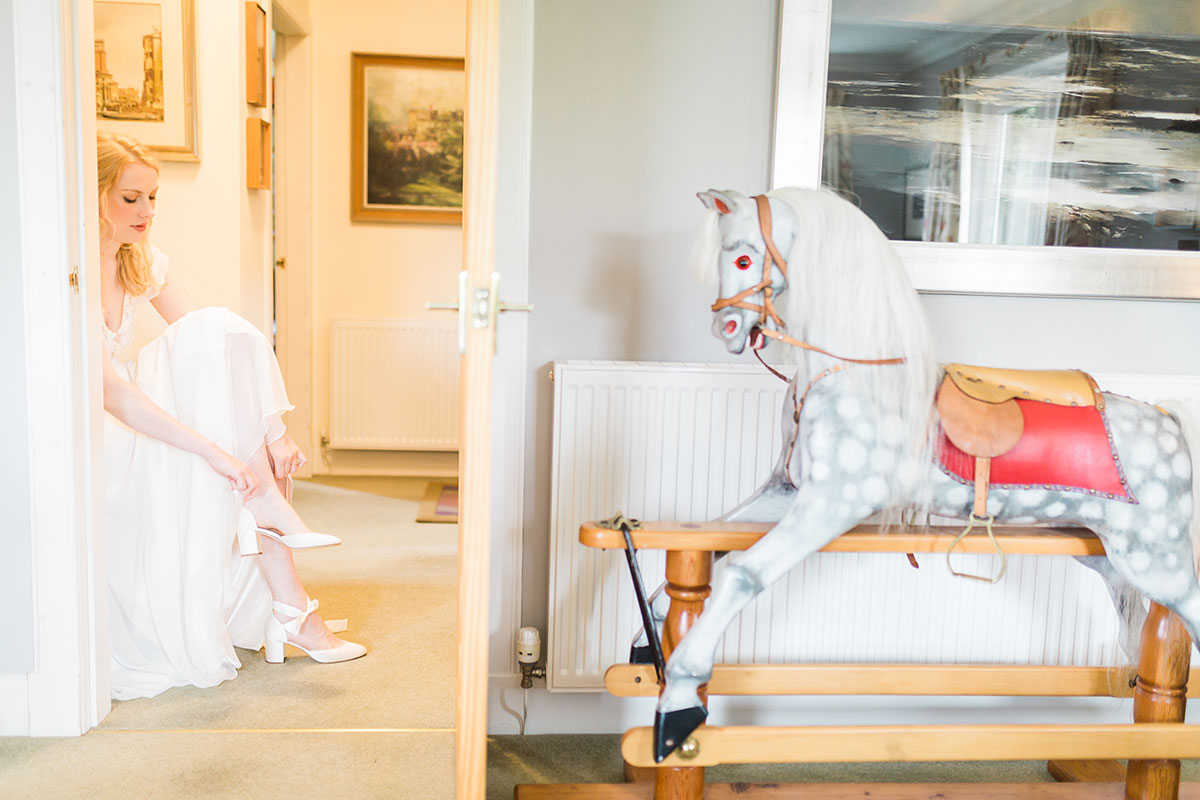 blonde bride fastening wedding shoe with rocking horse in foreground at Murthly Castle Perthshire