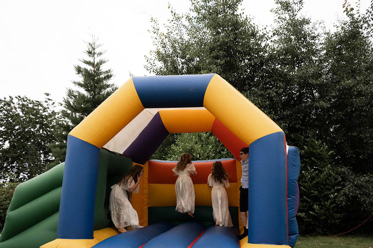 children on bouncy castle at Perthshire farm wedding