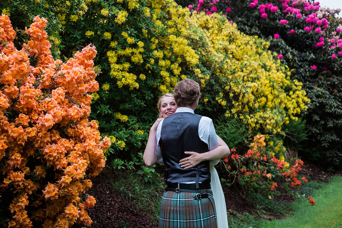 bride hugging groom surrounded by colourful bushes at Murthly Castle