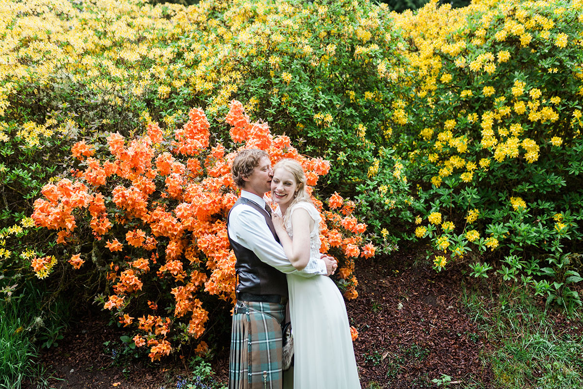 groom hugging laughing bride surrounded by colourful bushes at Murthly Castle