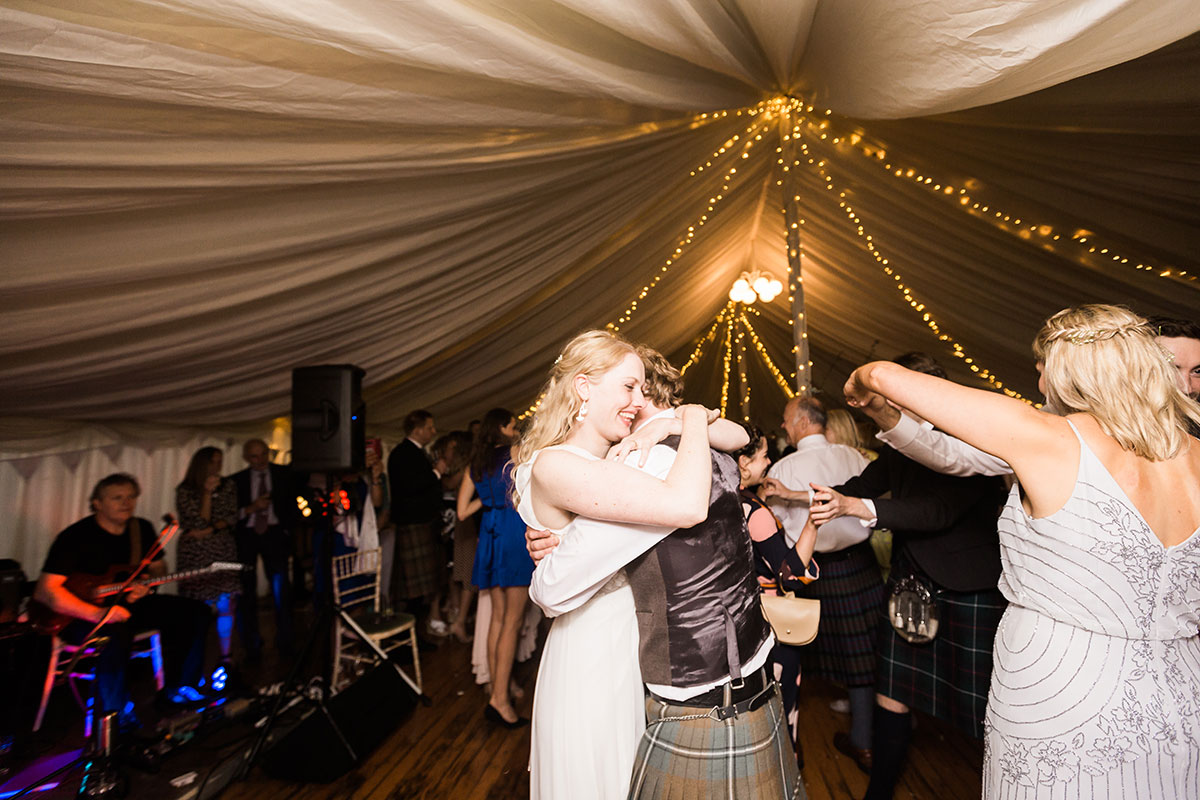 bride and groom hugging on dancefloor during first dance in marquee at Murthly Castle